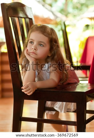 Thoughtful girl on chair - stock photo