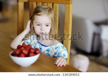 Thoughtful girl sitting next to fresh strawberries in a bowl - stock photo
