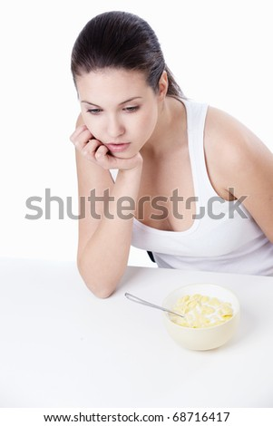 Thoughtful girl with a bowl of corn flakes on a white background - stock photo