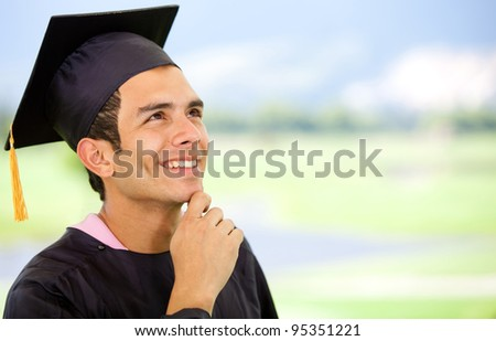 Thoughtful graduation man wearing a mortarboard and looking up - stock photo
