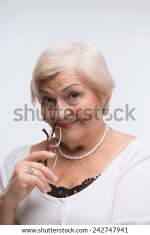 Thoughtful granny. Closeup portrait of a beautiful senior woman holding glasses by her chin and smiling at you standing over white background  - stock photo