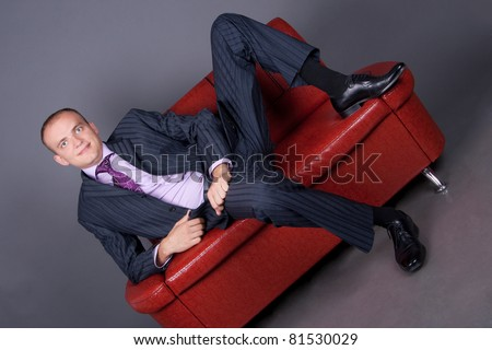 thoughtful guy in a suit sitting on a red couch - stock photo