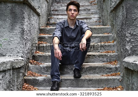 Thoughtful guy in gray clothes sitting on gray stairs - stock photo