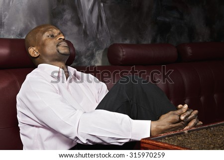 Thoughtful guy sitting on leather sofa and looking sideways - stock photo