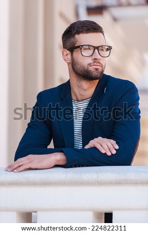 Thoughtful handsome. Handsome young man in eyeglasses and smart casual wear looking away while standing outdoors - stock photo
