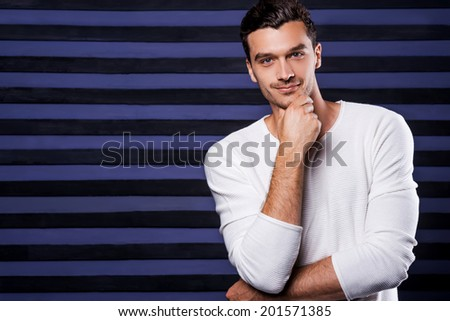 Thoughtful handsome. Handsome young man in white sweater holding hand on chin and looking at camera while standing against striped background - stock photo