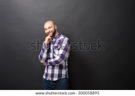 Thoughtful handsome. Handsome young smiling man in casual shirt holding hand on chin and looking at camera while standing against black background. - stock photo