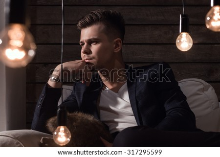 Thoughtful Handsome Man In Suit Sitting On Sofa Between Lamp On Wooden background - stock photo