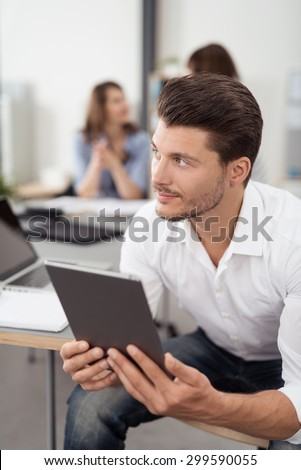 Thoughtful Handsome Man Sitting on a Chair Inside the Office, Holding his Tablet Computer While Looking Into the Distance. - stock photo