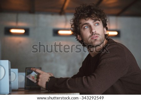 Thoughtful handsome pensive dreaming curly guy in brown sweetshirt sitting in cafe and using cellphone - stock photo