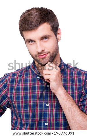 Thoughtful handsome. Portrait of thoughtful young man in casual shirt holding hand on chin and looking at camera while standing isolated on white - stock photo