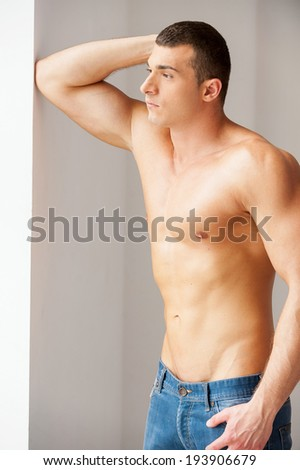 Thoughtful handsome. Thoughtful young muscular man looking away while standing near the window - stock photo