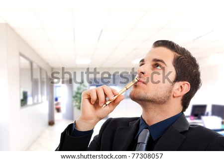 Thoughtful handsome young businessman holding a pen - stock photo