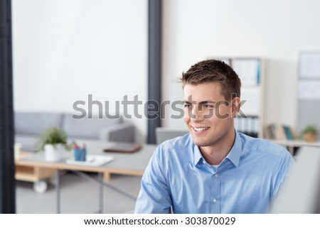 Thoughtful Handsome Young Businessman Sitting at his Desk, Looking Into the Distance with Happy Facial Expression. - stock photo
