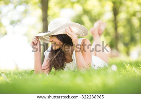 Thoughtful happy young woman holding sun hat while lying on grassland in park - stock photo