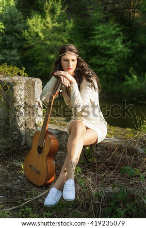 thoughtful hippie girl sits with his guitar by the river at sunset - stock photo