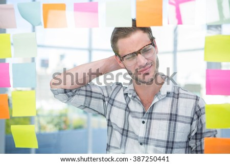 Thoughtful hipster man with post-it in office - stock photo