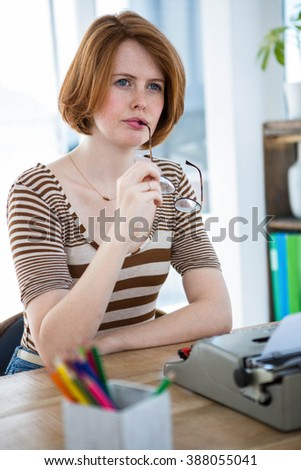 thoughtful hipster woman, sitting at her desk with a typewriter - stock photo