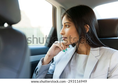 thoughtful indian business woman sitting in car backseat - stock photo