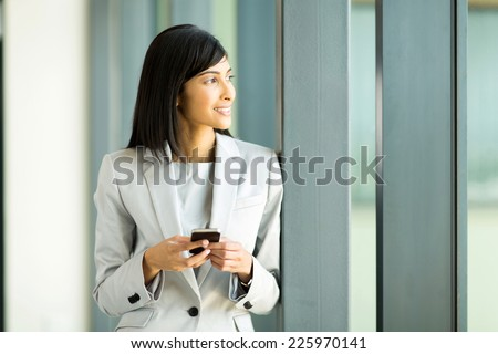 thoughtful indian businesswoman holding smart phone in office - stock photo