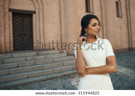 thoughtful indian lady in white leather dress against ancient building. She standing in shade but lightened by reflected morning sunlight. Light falls down on stairs and paving stones of sidewalk - stock photo