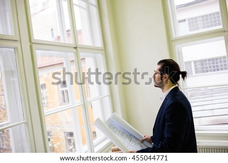 Thoughtful interior designer holding blueprint while looking through window in office - stock photo