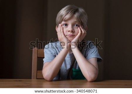 Thoughtful little boy sitting at the desk - stock photo