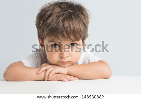 Thoughtful little boy with sad expression is hopeless and sorry about his problems. Closeup headshot - stock photo