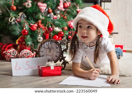 Thoughtful little girl in Santa hat writes letter to Santa Claus near christmas tree - stock photo