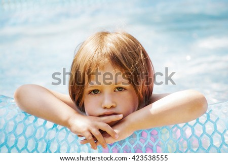 Thoughtful little girl in the pool, outdoor. - stock photo