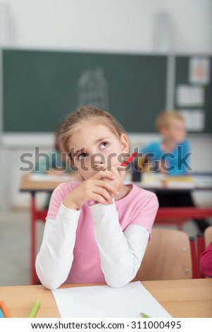 Thoughtful little girl sitting at her desk in primary school during art class thinking of a subject to draw staring up into the air seeking inspiration - stock photo