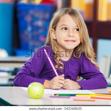 Thoughtful little girl with sketch pen and paper sitting at desk in classroom - stock photo