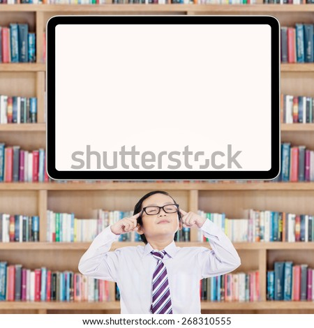 Thoughtful little schoolboy looks thinking an idea under empty whiteboard in the library - stock photo