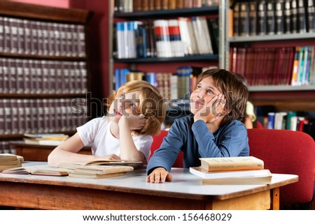 Thoughtful little schoolboys looking away while sitting at table in library - stock photo