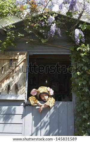 Thoughtful little young boy in jaguar costume in shed - stock photo