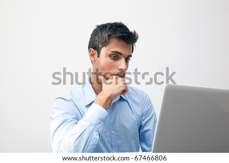 Thoughtful looking businessman in front of his laptop - stock photo