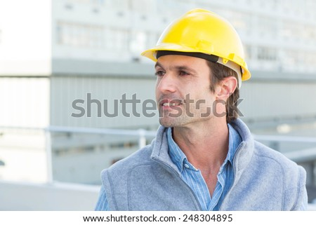 Thoughtful male architect wearing yellow hard hat outdoors - stock photo