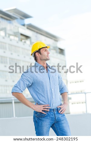 Thoughtful male architect with hands on hips outdoors - stock photo
