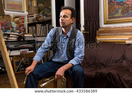 Thoughtful male artist waiting for inspiration  sitting in his studio or gallery holding  paintbrushes and a rag - stock photo