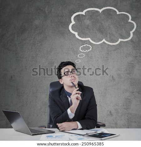 Thoughtful male entrepreneur looking at a cloud tag while imagines his ideas - stock photo