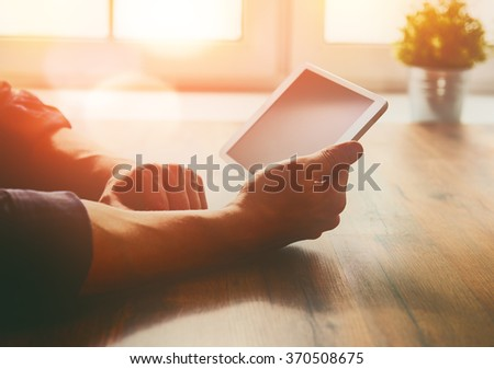 Thoughtful male person looking to the digital tablet screen while sitting at the table. - stock photo