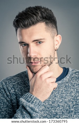 Thoughtful man close up portrait against dark background.  - stock photo