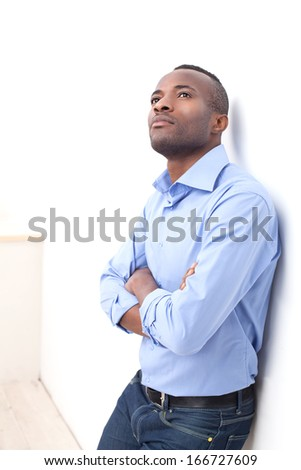 Thoughtful man. Handsome young black man keeping his arms crossed and looking up while leaning at the wall - stock photo
