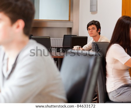 Thoughtful man having a coffee while looking at the camera - stock photo