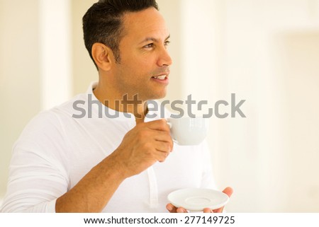 thoughtful man having cup of coffee indoors - stock photo