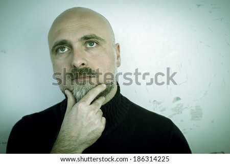 Thoughtful man in front of a wall - stock photo