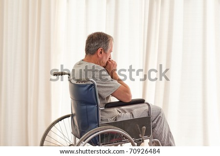 Thoughtful man in his wheelchair at home - stock photo