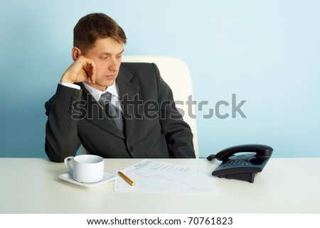 thoughtful man in the office looks at the phone - stock photo