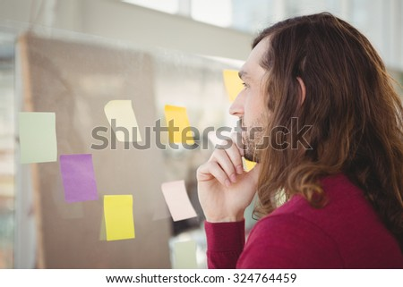Thoughtful man looking at adhesive notes stuck on glass in office - stock photo