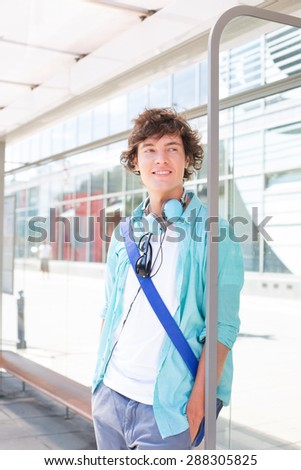 Thoughtful man looking away while waiting at bus stop - stock photo